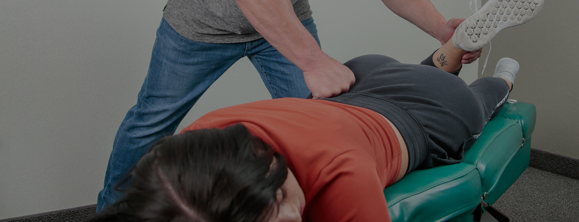A female patient lying face down on an adjustment table while Dr. Day performs a lower back treatment.